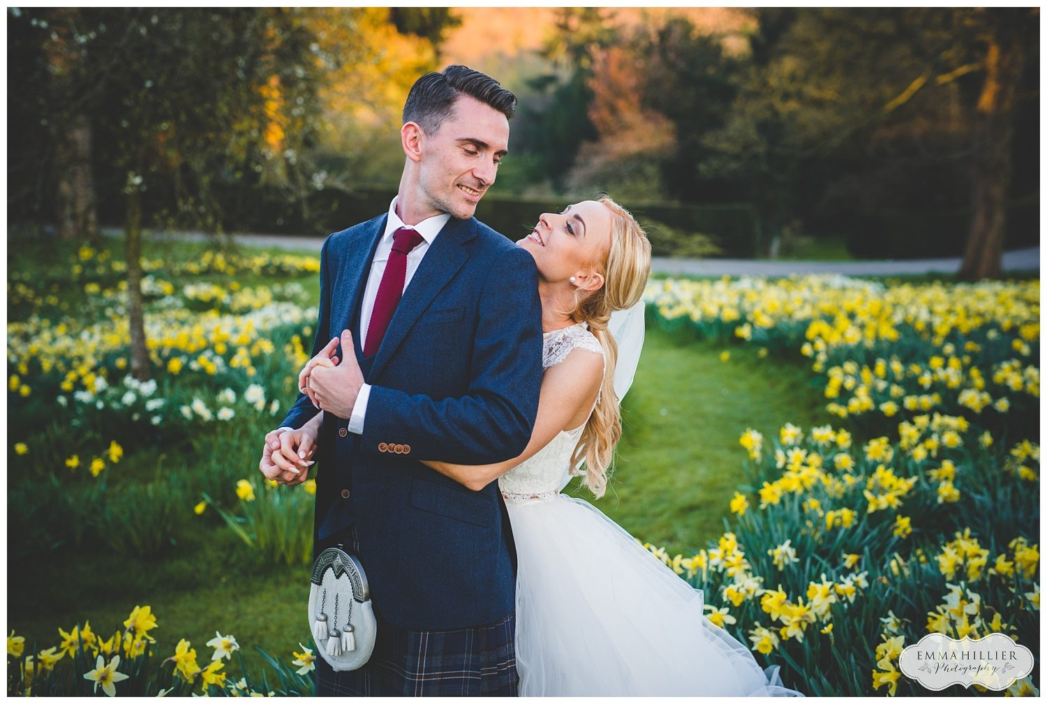 Bride and groom in a field of daffodils at Askham Hall