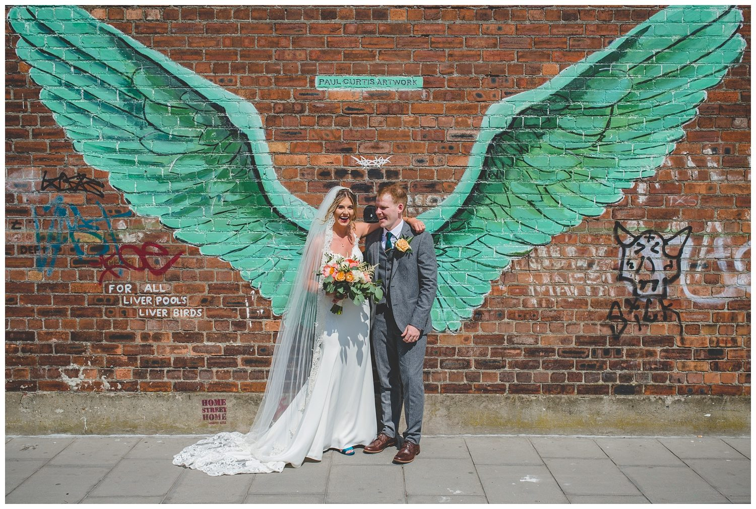 bride and groom with Paul Curtis wings