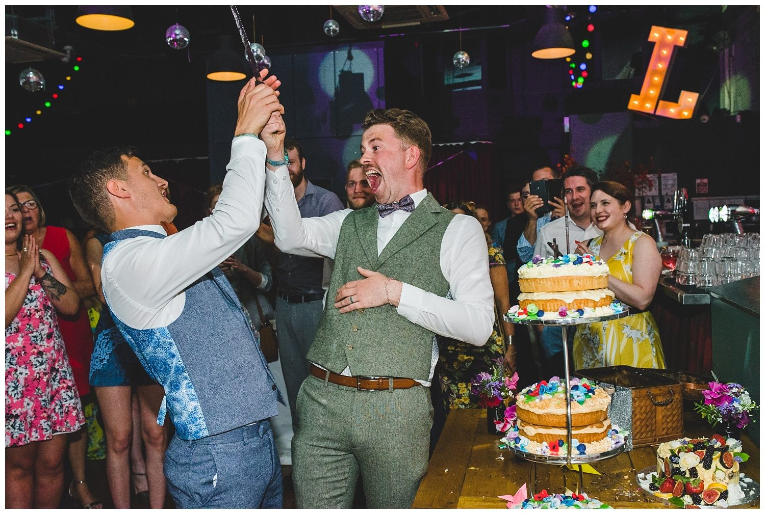 Two happy grooms cut the cake at their Leaf wedding in Liverpool