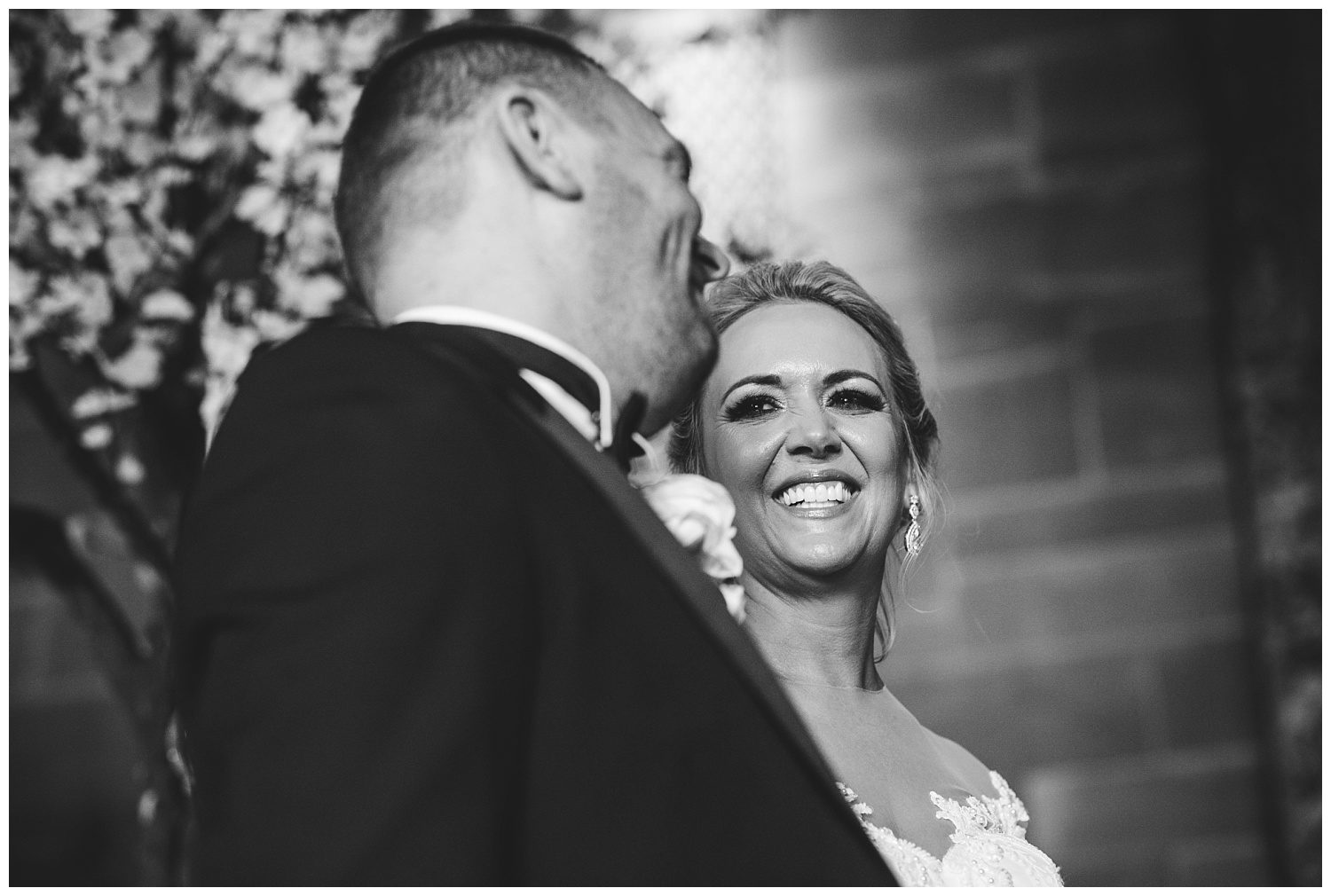 Bride smiling at the groom during their Peckforton Castle wedding ceremony