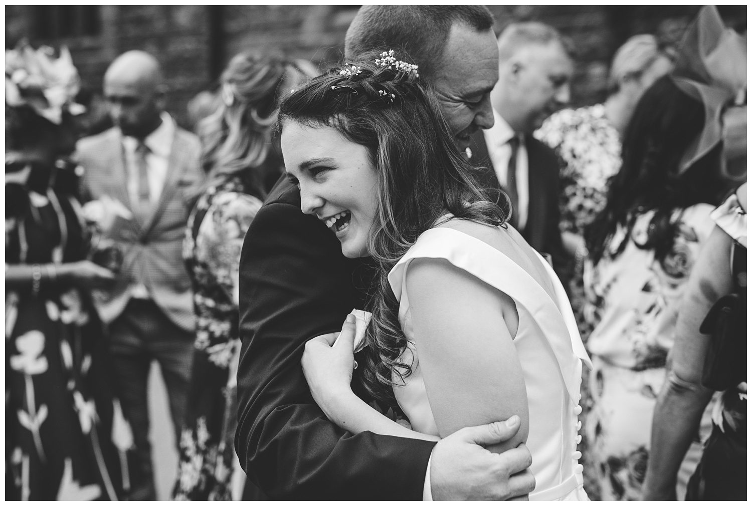 Groom hugging his daughter at Peckforton Castle wedding