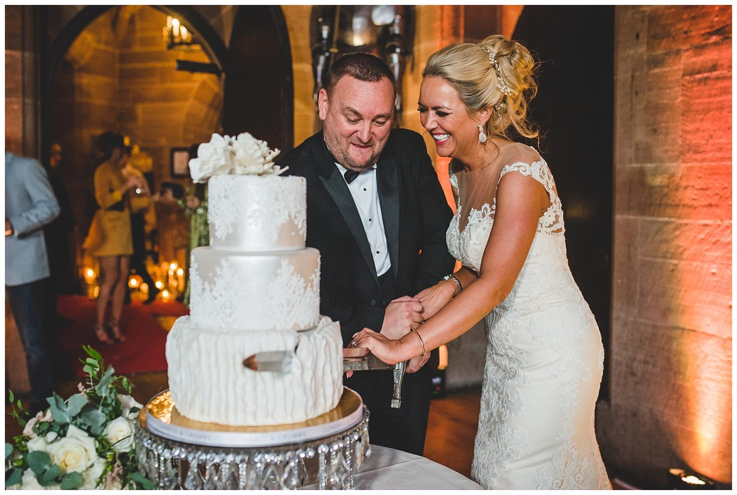 Bride and groom cutting the cake at Peckforton Castle