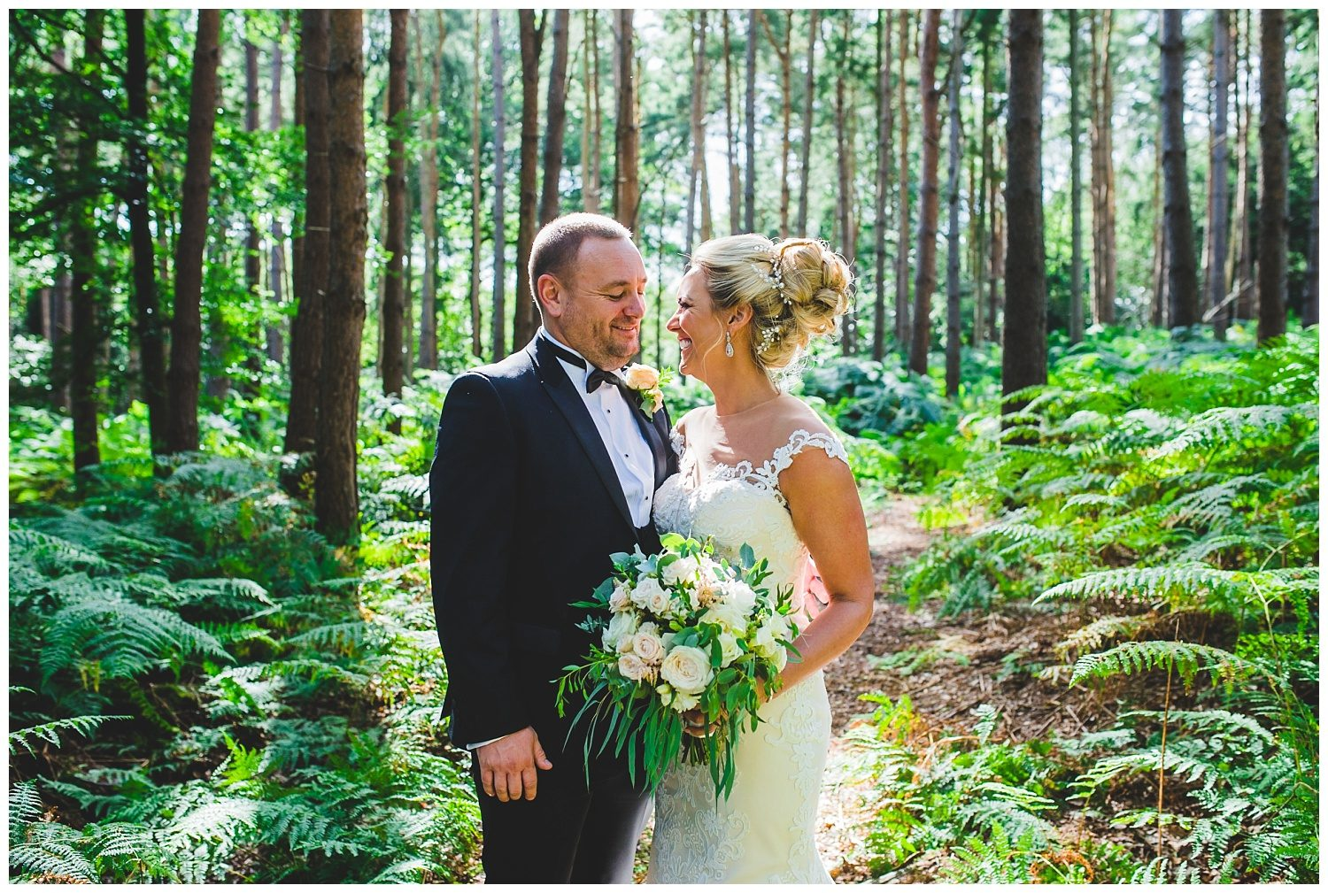 Bride and groom laughing in the woods at Peckforton Castle