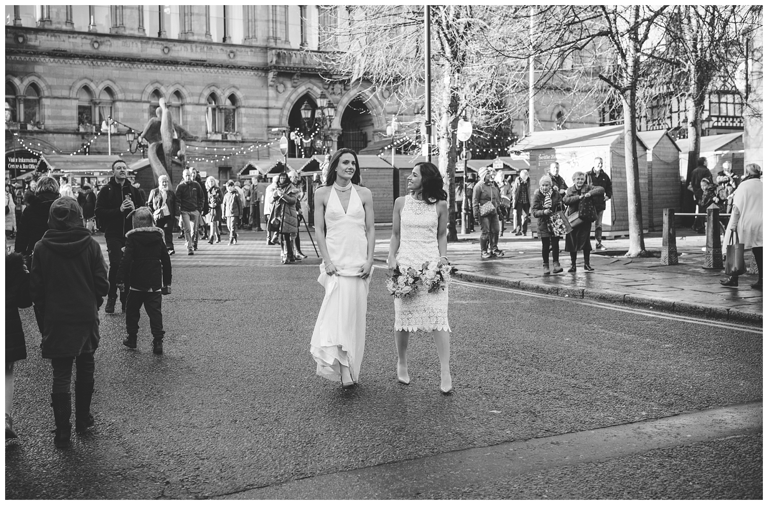 Two happy brides walking through Chester
